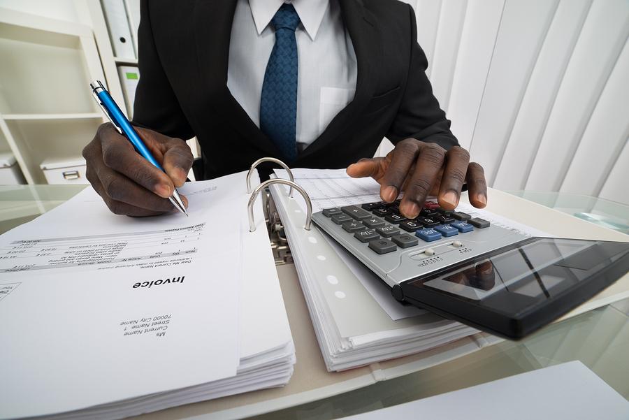bigstock-Businessman-Calculating-Invoic-93758564